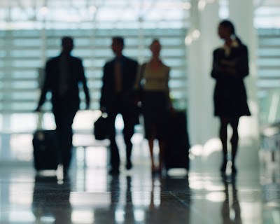 Businesspeople Walking Through Airport with Luggage
